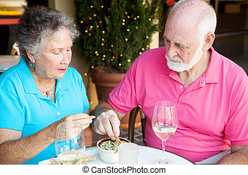 Serious Senior Diners - Senior couple dining out, looking...