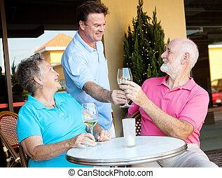 Waiter Serves the Wine - Waiter serving wine to a senior...