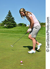 Body English Putt - A woman golfer applies body english on a...