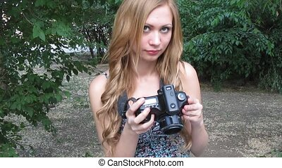 Young beautiful woman with a digital camera DSLR in hands