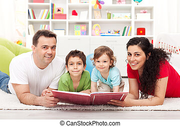 Young family with two kids reading a story book
