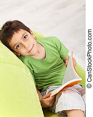 Young boy reads a book