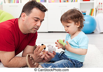 Father and toddler son playing on the floor with finger...