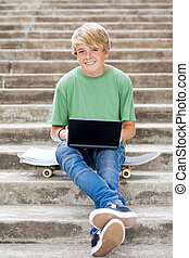 cute teen boy with laptop outdoors