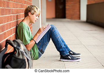 teen high school student reading book in school passage