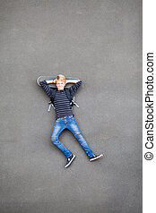 overhead view of teen skateboarder lying on his skateboard