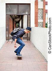 teen boy skateboarding in school passage