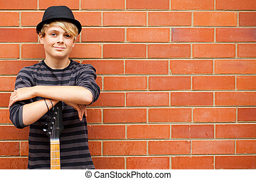 handsome teen boy with guitar outdoors