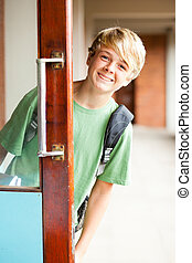 cute high school boy behind classroom door