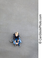 teen boy sitting on skateboard