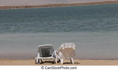 Dead sea landscape - Beach lounger and a plastic chair on...