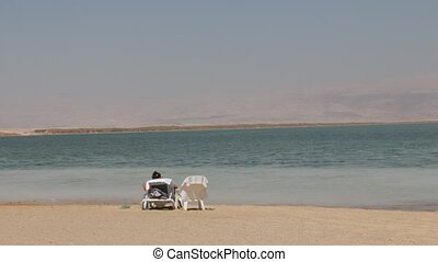 Dead sea landscape - Tanned young beautiful girl on beach...