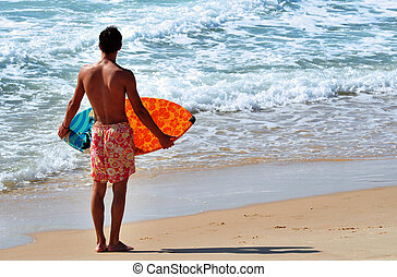 Sea Sport - Skimboarding - A boy skimboarding in the ocean