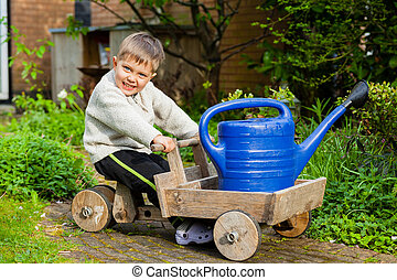 Cute boy plays with toy tools in the garden.