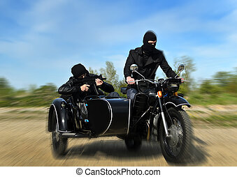 Two armed men riding a motorcycle with a sidecar Motion blur...