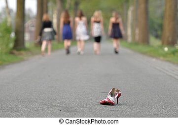 Left pair of shoes - A group of teen girls with a pair shoes...