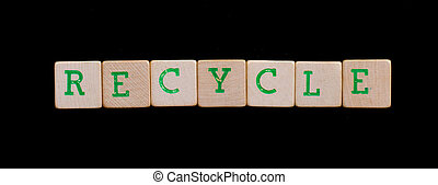 Green letters on old wooden blocks recycle