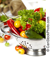 Fresh vegetables in metal colander over white