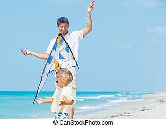 boy with father on beach playing with a kite - Little cute...