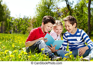 Leisure  - Three happy friends reading on the lawn