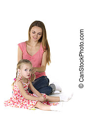 Pretty woman brushing her daugther's hair against a white...