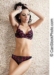 girl in fashion lingerie on carpet with both hands on the head