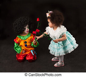 little girl giving flowers small clown