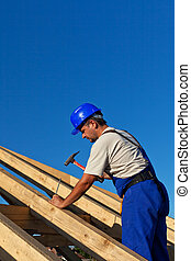 Carpenter building roof structure - driving in large nail