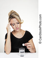 dont feel good - woman at her desk about to take a soluble...