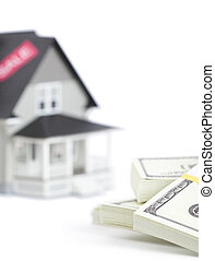 Bundles of dollars in front of house architectural model, isolated