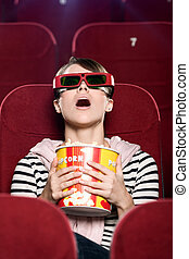 3D movies - Young woman in 3D glasses watching a movie