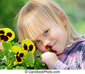GIrl with flowers - Little girl smelling flowers in a garden