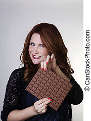 indulge yourself - woman holding up a large bar of chocolate
