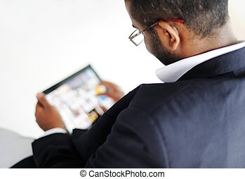 Handsome African American man with tablet computer