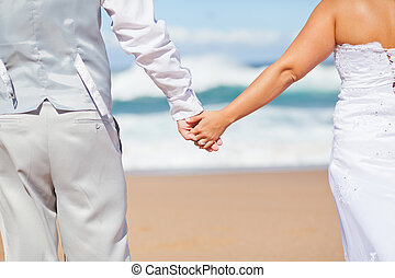 groom and bride holding hands on beach - rear view of groom...