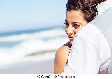 young woman hugging husband on beach