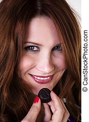indulge yourself - woman about to eat a bit of chocolate
