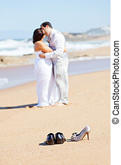 groom kissing bride on beach
