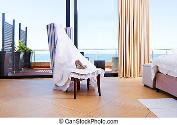 bridal wedding dress and shoes on a chair with sea view...