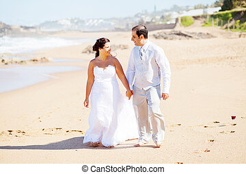 happy groom and bride walking on beach
