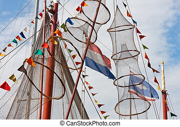 fishing ship decorated with nets and flags from holland and...