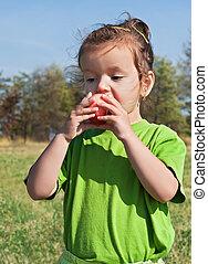 Little girl eating apple - Beautiful little girl eating red...