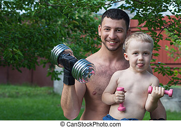 Father and son train with dumbbells outdoors