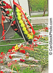 Flowers and memorial wreath are on the ground
