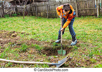 Boy digging in the ground - Boy digging on a grass field in...