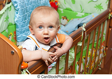 Baby standing in crib - Baby boy standing in cot (crib) and...