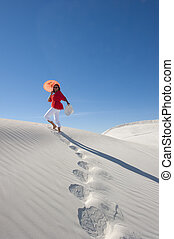 Attractive woman leaving footsteps up a sanddune - Upward...