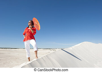 Confident woman on desert sand dune - An attractive and...