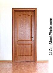 Brown door in white wall - Closed brown wooden door in white...