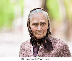 Old woman with kerchief outdoor - Closeup portrait of a...